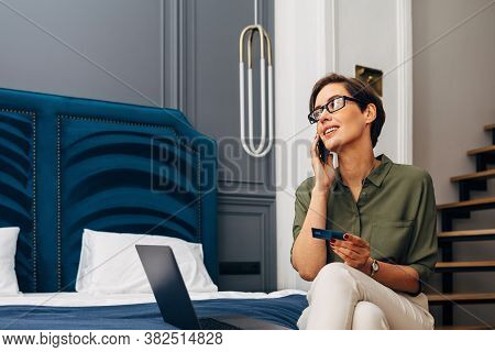 Mid Adult Woman Talking On Mobile Phone And Holding A Credit Card. Businesswoman Making Online Order