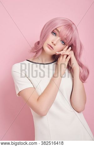 Cute Girl With Long Pink Hair, Hair Coloring. Beautiful Woman On A Pink Background In A White Dress.