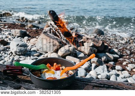 Eat Fried Eggs From A Frying Pan On The Beach, A Delicious And Healthy Breakfast In A Camping In The