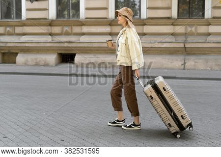 Tourist Woman With A Suitcase Down The Street In A European City, Tourism In Europe. Walks Down The