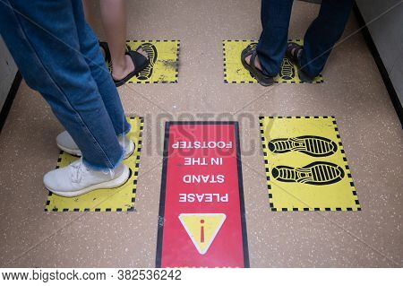 Foot Of Peoples Standing On Yellow Footprint Sign In Lift Or Elevator And Keep Space For Avoid Sprea