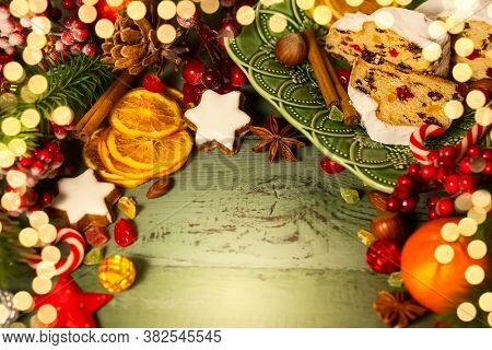 Holiday concept with Christmas stollen, cookies, spices, fruits and fir tree branches on the green wooden background.