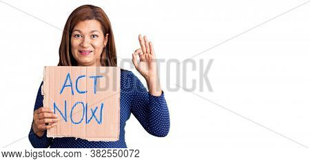 Middle age latin woman holding act now banner doing ok sign with fingers, smiling friendly gesturing excellent symbol