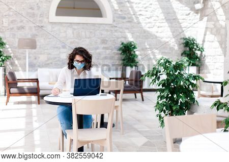 Young Woman Working Safety In Cafe Indoors. Social Distancing During Quarantine. Freelancer Wearing