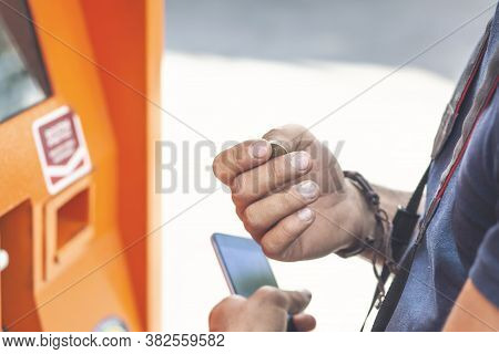Man Holding A Coin On A Blurred Atm Machine Background.