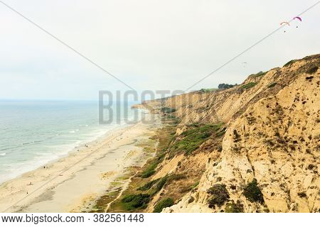 Large Rugged Bluffs Including Paragliders Gliding Above Overlooking The Secluded Public Beach And Pa
