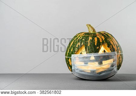New Normal Concept. Funny Smiling Halloween Pumpkin In A Protective Medical Mask On A Gray Backgroun