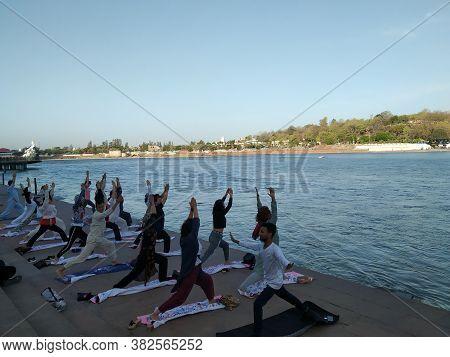 Rishikesh, Uttarakhand/india- June 21 2019: People Doing Yoga On The Banks Of Ganga River, Internati