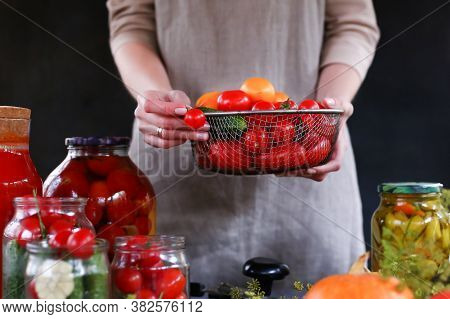 Woman In Linen Apron With Hands Holding Bowl Of Homemade Fresh Vegetables. Food Preservation During