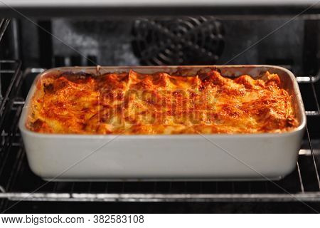 italian lasagne with cheese cooking in the oven