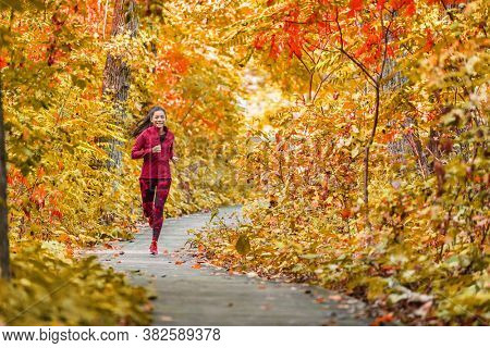 Autumn forest run path. Fall trail runner woman running in beautiful foliage woods nature background. Asian happy sports woman training outdoor.