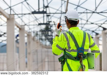 Asian Engineer Technician Watching Construction Control In The Construction Of Roof Structures On Co