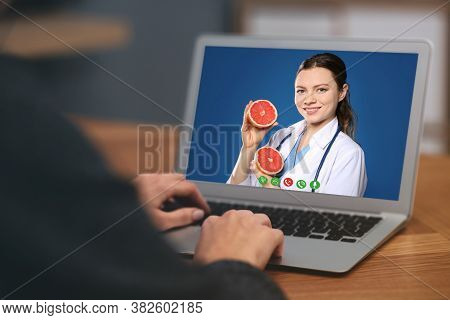 Woman Using Laptop For Online Consultation With Nutritionist Via Video Chat, Closeup