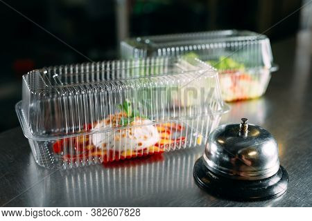 Food Delivery. Distribution Table In A Restaurant With A Metal Bell. Food In Plastic Containers. Pan