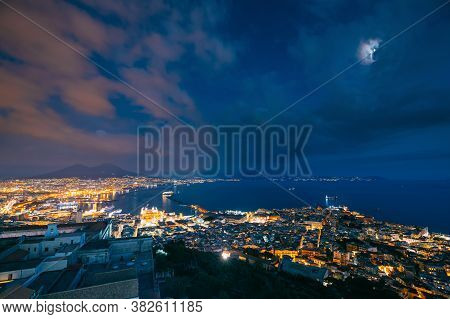 Naples, Italy. Top View Skyline Cityscape In Evening Lighting. Tyrrhenian Sea And Landscape With Vol