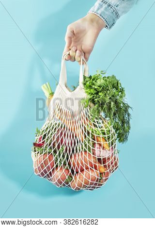 Mesh Bag With Vegetables And Herbs In Female Hand. Woman Hold String Net Shopping Bag On Blue Backgr