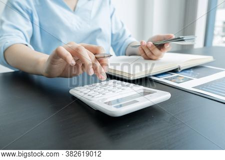 Women's Hands Hold A Dollar And Using A Calculator Calculate Graphs To Build Successful And Economic