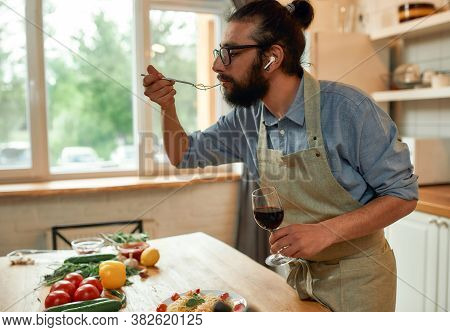 Awesome Taste. Young Man In Apron, Cook Holding Glass Of Wine While Eating Pasta In The Kitchen At H