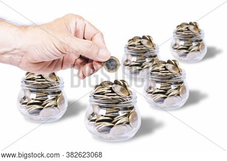 Male Hand With A Euro Coin On A Glass Jar Full Of Euro Coins, Other Defocused Glass Jars, On White B