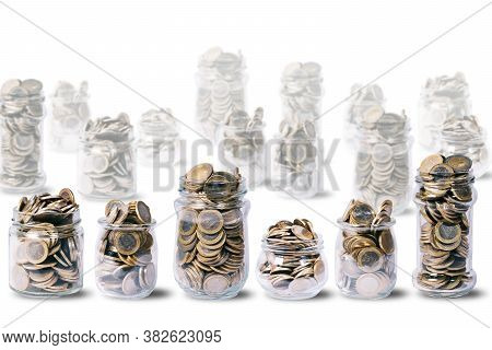 Some Glass Jars Full Of Euro Coins, Other Glass Jars Out Of Focus, On White Background With Copy Spa