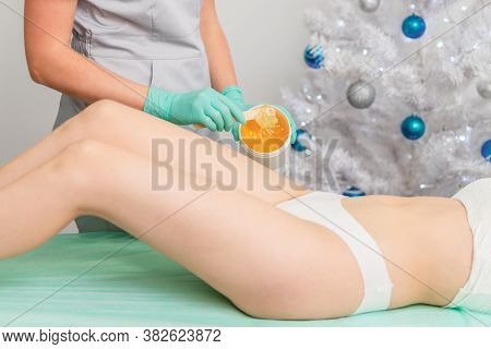 Young Woman Getting Wax Epilation Of Legs. Depilation Concept. Product Waxing Bowl. Christmas Discou