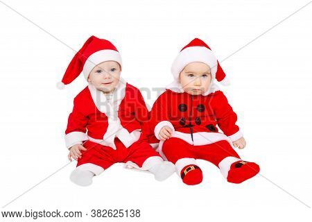 Two Adorable Young Babies Are Sitting In The Santa Claus Suit And Hat. Space For Text. Happy Santa B