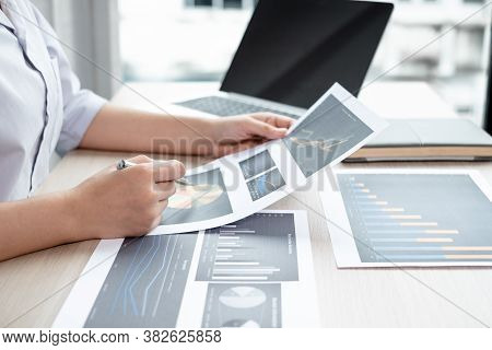 The Hands Of A Male Businesswoman Are Analyzing And Calculating The Annual Income And Expenses In A