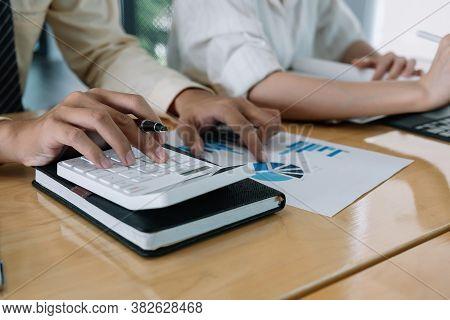Businessman Using Calculator For Do Math Finance On Wooden Desk In Office And Business Working Backg