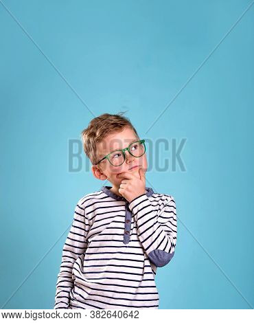 School Boy Is Daydreaming. Thinking Nerd Kid Wearing Glasses, Isolated Over Blue