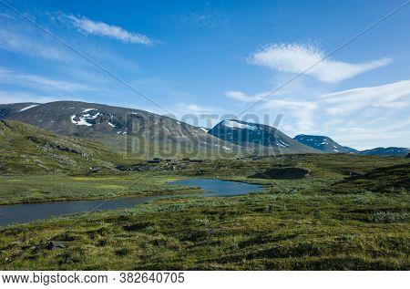 Swedish Lapland landscape. Arctic environment of Scandinavia in warm summer sunny day with blue sky. Alesjaure on Kungsleden and Nordkalottruta Arctic hiking Trail in northern Sweden