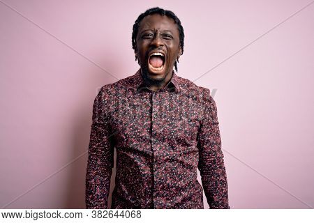 Young handsome african american man wearing casual shirt standing over pink background angry and mad screaming frustrated and furious, shouting with anger. Rage and aggressive concept.