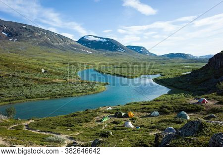 Hiking in northern Sweden. Camping at Alesjaure on Kungsleden and Nordkalottruta Arctic hiking Trail. Swedish Lapland landscape. Arctic environment of Scandinavia in summer sunny day