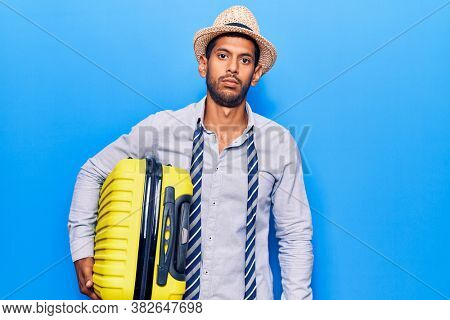 Young latin man wearing summer hat holding cabin bag thinking attitude and sober expression looking self confident