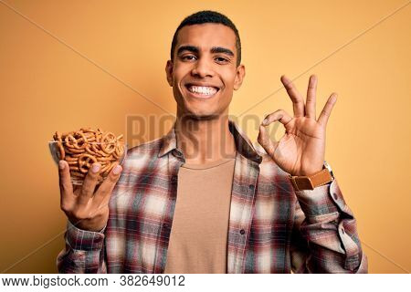 Young handsome african american man holding bowl with german baked pretzels doing ok sign with fingers, excellent symbol