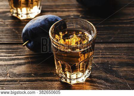Slivovica - Plum Brandy Or Plum Vodka, Balkan Hard Liquor, Strong Drink In Shot Glasses On Old Woode