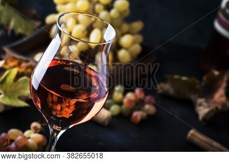 Rose Wine At Wine Tasting Concept. Gray Background With Grape And Leaves. Pink Wine In Wineglass. Co