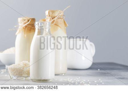 Vegan Rice Plant Based Milk In Bottles, Closeup, Gray Background. Non Dairy Alternative Milk. Health