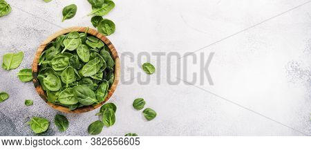 Fresh Baby Spinach Leaves In Wooden Bowl On Gray Stone Table. Top View, Copy Space