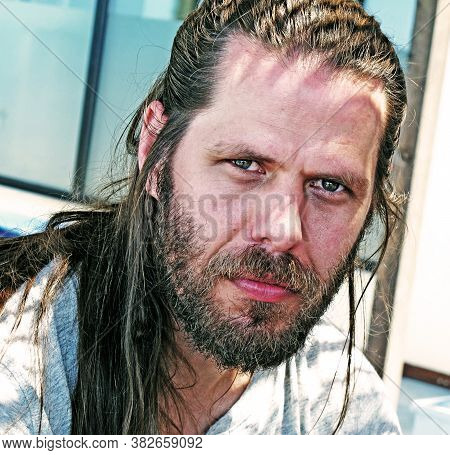 Saint Paul's Bay, Malta - June 8, 2012: Man With Long Hair And Intense Eyes