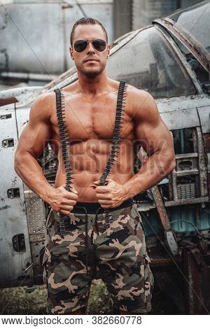 Muscular American Soldier With Stationary Airplane Behind. Brutal Man With Large Biceps And Naked To