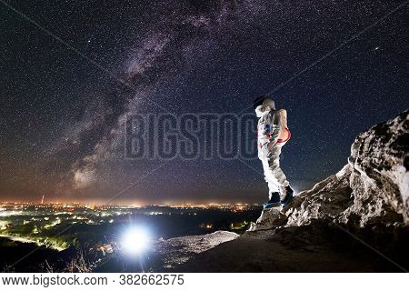 Side View Of Brave Space Traveler Standing On Rocky Mountain Under Night Sky With Stars. Mission Spe