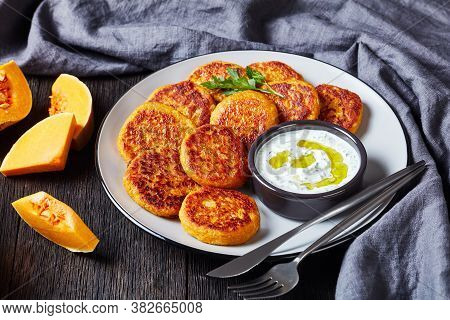 Low-calorie Baked Butternut Squash Pancakes With Greek Yogurt Tzatziki Sauce On A Plate With Parsley