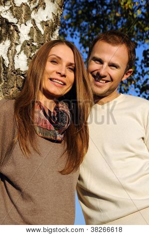Young couple under a tree in autumn
