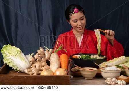 Asian Women Wearing Korean Traditional Costumes (hanbok) Are Mixing Fresh Stir-fry And Kimchi Ingred