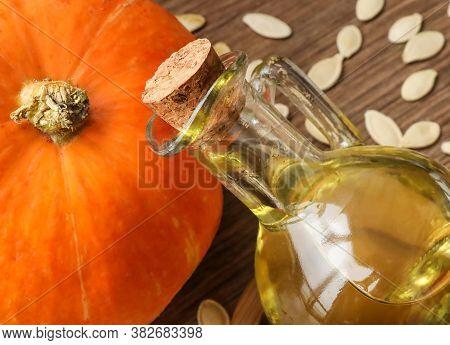 Pumpkin Oil In A Bottle, Pumpkin, Pumpkin Seeds On A Background Of Wood Texture.