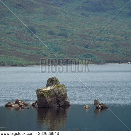 Scottish Landscape With A Large Rock In A Mountain Lake In The Foreground. Loch Arklet, Scotland