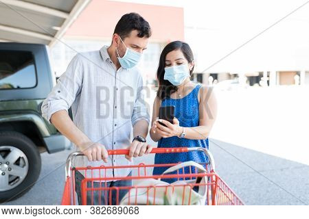 Couple In Protective Face Masks Checking Grocery List On Smart Phone At Parking Lot