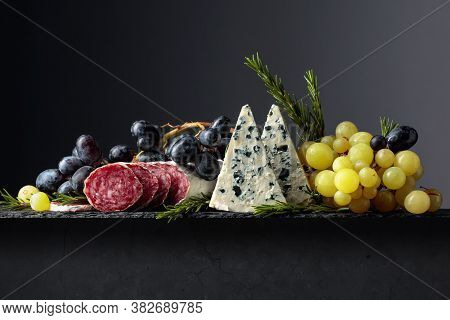 Blue Cheese, Dry-cured Sausage, Grapes, And Rosemary On A Black Background. Simple And Tasty Food. C