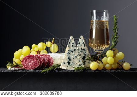 White Wine And Snacks On A Black Background. Glass Of Wine, Blue Cheese, Dry-cured Sausage, Grapes,