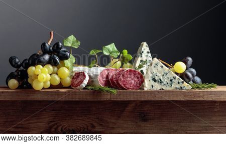 Blue Cheese, Dry-cured Sausage, Grapes, And Rosemary On An Old Wooden Table.  Simple And Tasty Food.